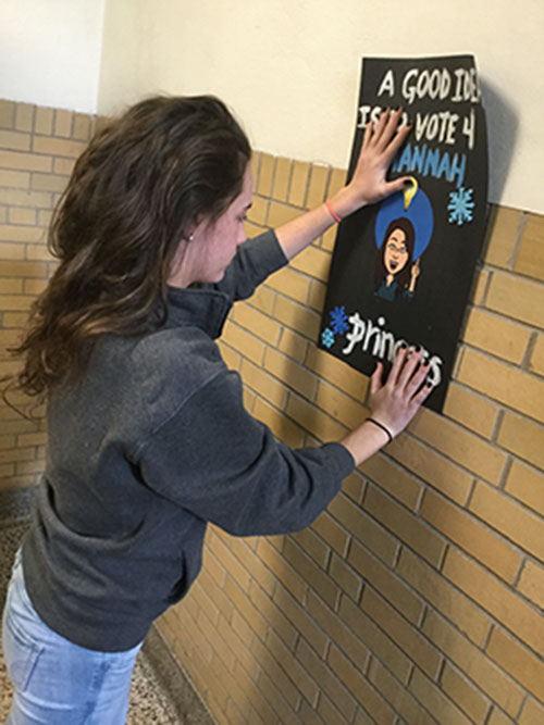 "Junior Hannah Joyce hangs up her Winter Carnival poster. Each candidate who ran for Winter Carnival put up posters around the school to try to win over students.""The bitmoji are very popular; I thought it would be a good way to incorporate it into my posters to make them catchy and funny,"" Joyce said."