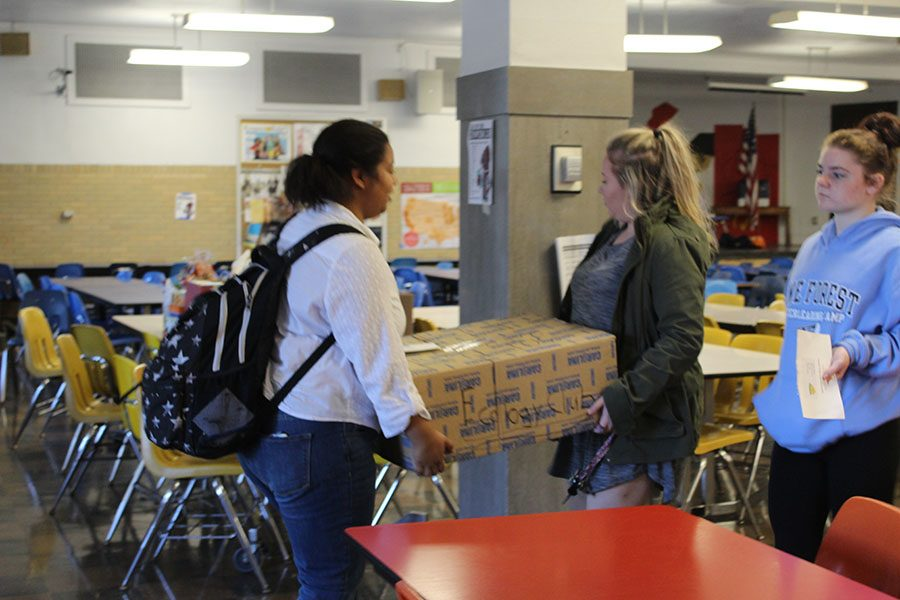 """Delivering baskets for Ecology Club, seniors Tayah Moore, Rhiannon Daniels and Holly Wenner carry boxes of food out to their car. All three girls delivered baskets for Thanksgiving and plan on doing the same for Christmas. """"I love getting the opportunity to deliver food baskets for the holidays. It's a really humbling experience that makes you feel good inside,"""" Daniels said."""
