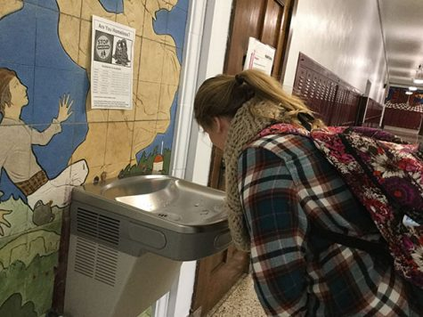 """While bending down to the water fountain on the third floor, junior Hannah Duncan drinks out of the fountain. Students are not allowed have water bottles on them, so they must drink out of the fountain. """"I don't like drinking out of the water fountains because they are dirty and people put their mouths on them."""" junior Hannah Duncan said. """"The water does not taste bad, but I would just rather bring a water bottle in my bookbag."""""""