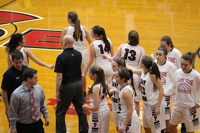"""HUDDLE – During a timeout, the girls' basketball team listens closely to their coaches' suggestions. The girls won their December 23 game against Pine Grove 53-38. """"I hope to really improve the upcoming season as a team,"""" junior Olivia Eckert said."""
