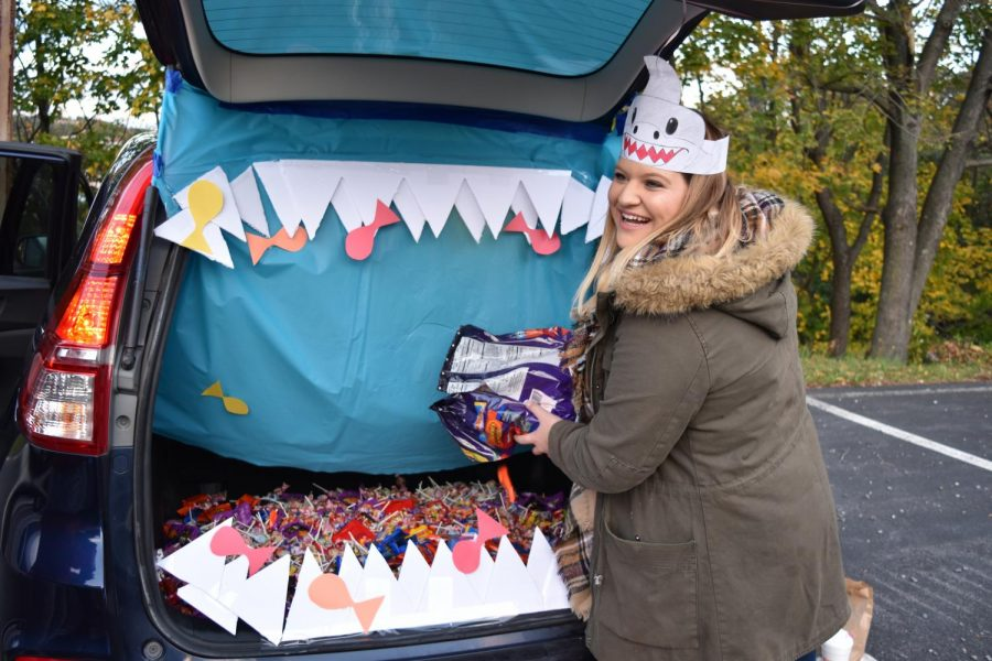 """FILL-UP - Senior Hannah Duncan fills up Alpha Iota Delta's car, stylized as a shark with sharp foam teeth and paper fishes. """"My favorite part about Trunk-or-Treat was definitely handing out candy to the little kids,"""" Duncan said. """"I loved all of their costumes, and it just reminded my of my childhood."""""""