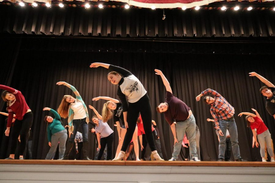 """Members of the Drama Club stretch before rehearsing for their musical. The Drama Club presented How to Succeed in Business Without Really Trying in March, and according to Mrs. Maria Malek, Drama Club adviser and English teacher, audience numbers are lower in years when the musical does not have high name recognition. """"Our audience numbers were not as high as they were in previous years,"""" Mrs. Malek said."""
