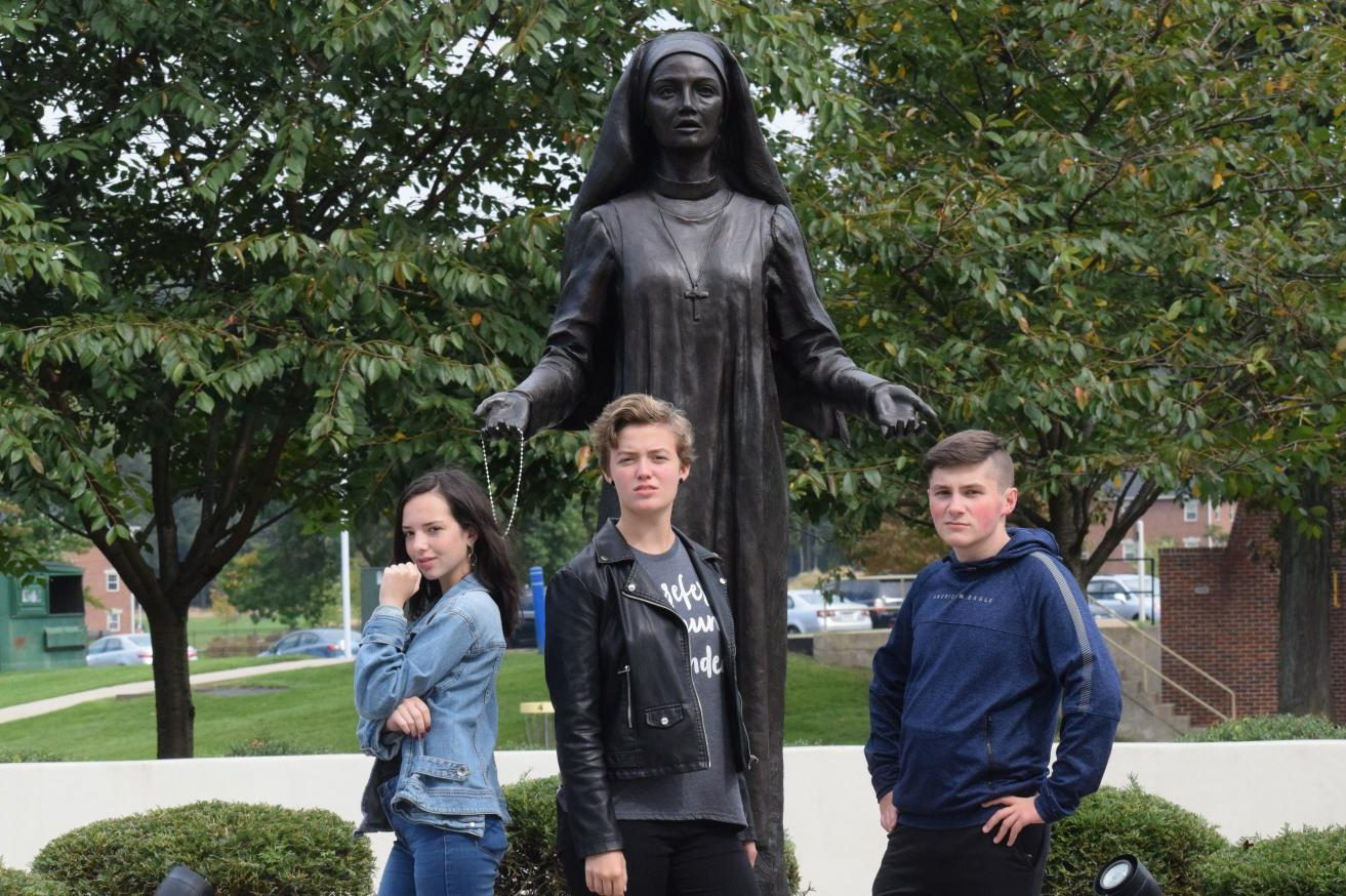 """In front of a statue of Jane Frances de Chantal, sophomores Lily McDonald, Kendra Speak, and Jake Montgomery pose for the camera. The Drama Club, Stage Crew, and Dramatic Literature class went on a field trip to DeSales University to watch a Shakespeare play. """"It was nice to see profesional actors so we can learn from them and do better. The show was good and fresh,"""" Autumn McDonough, senior said."""