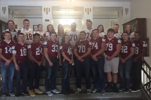 Senior football players pose with the teachers who have inspired them throughout high school.