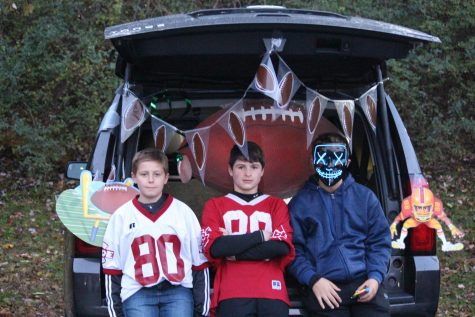 "Henry Mohl (middle) stands at his football themed vehicle. He said, ""This event is pretty cool and it's safer than normal trick-or-treating."""