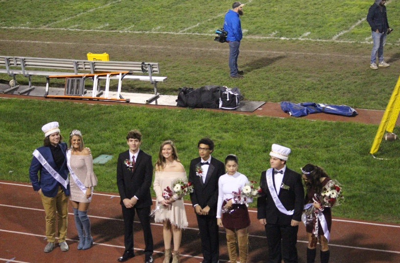 "The 2018 Homecoming Court poses for the crowd at the October 12 varsity football game. Senior Samantha Day and Bernie Guzick were crowned the 2018 Homecoming king and queen. ""When I won, I was so thankful because I put a lot of time into campaigning and overall just happy to have the experience,"" Day said. ""It was honestly one of the best experiences I've ever had being crowned, and I was blessed to have so many people there supporting me."""