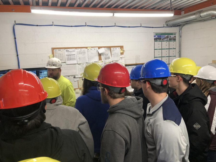 One of the workers of the control room shows students how the beams are made and moved from inside the control booth.