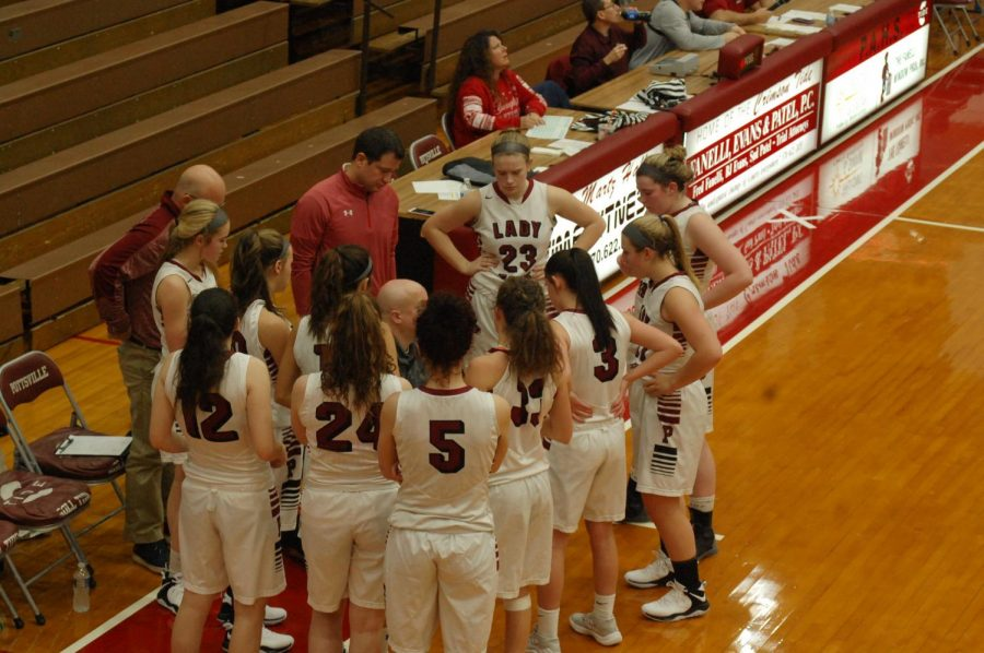 The girls varsity basketball team discusses the game during a timeout.