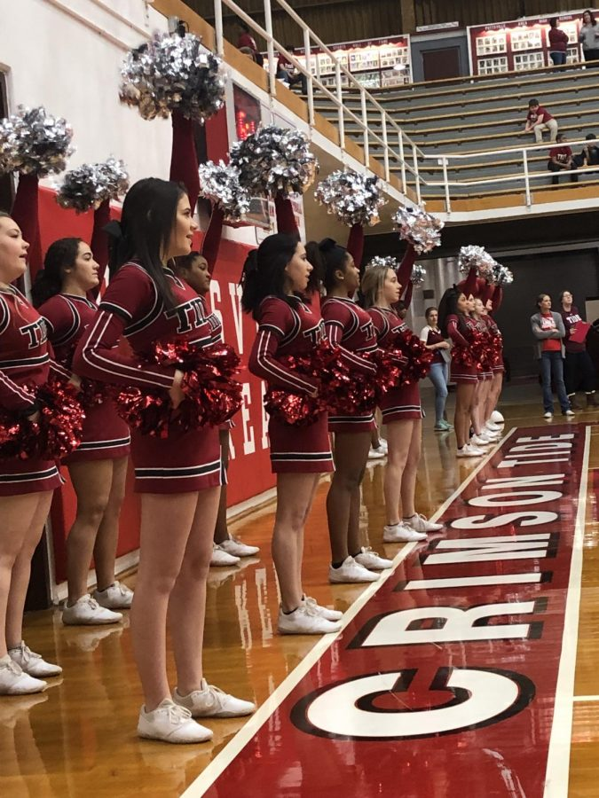 The cheerleading squad cheers for the basketball teams while they play.