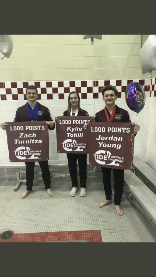 "Zachary Turnitza, Kylie Tohill, and Jordan Young all stand together holding their banners. They just finished competing in the 2019 District XI Swimming Championships. Senior Zach Turnitza said, ""You need to have a strong team to achieve 1,000 points."""