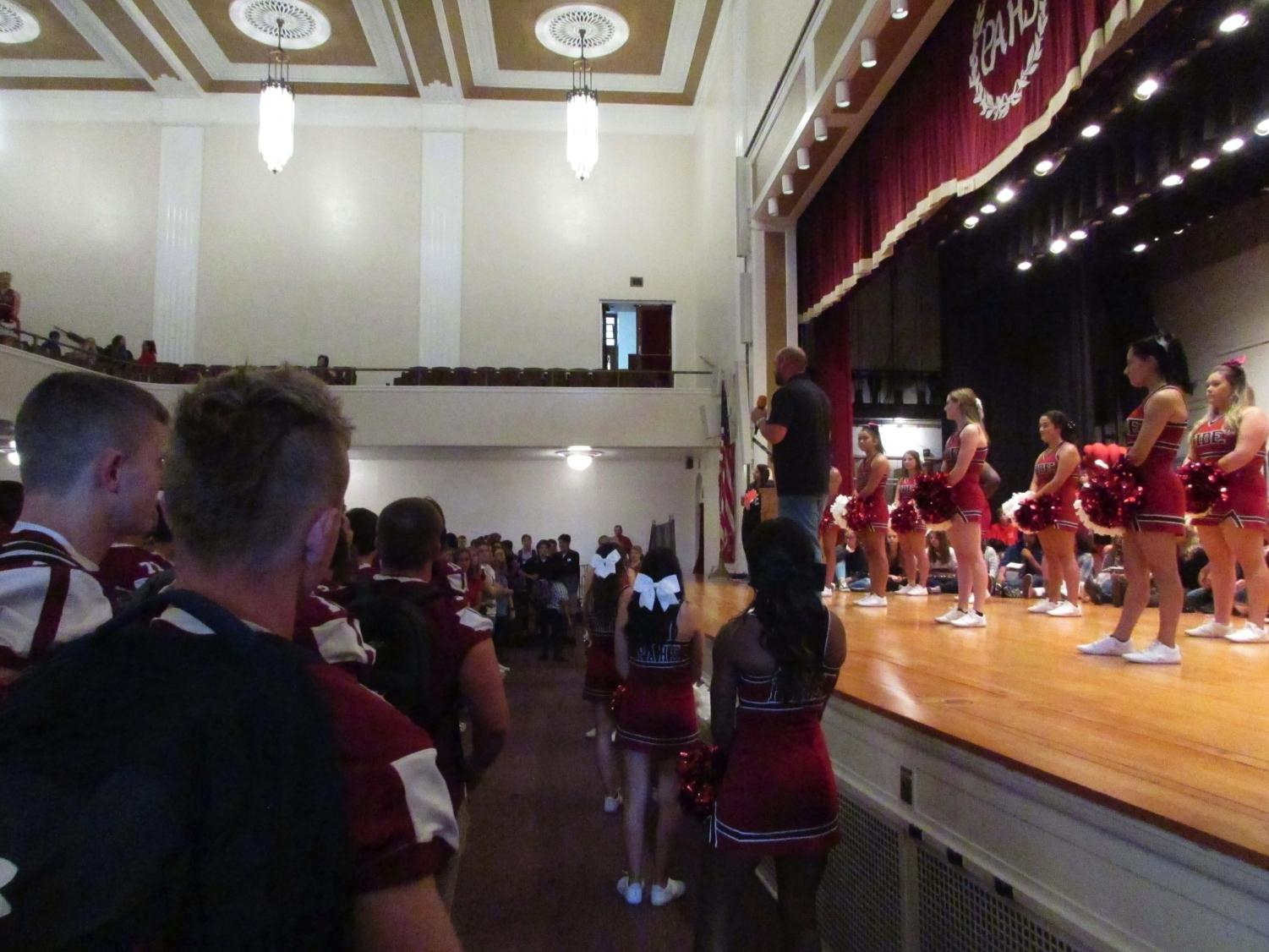 """PAHS cheerleaders perform at the first pep rally. Some of the cheers they showed were """"Give a Yell"""" and """"Go Big Red.""""  Senior Isabella Woodford [in the audience] said, """"The pep rallies before the game are most memorable and one of the best parts of the week."""""""