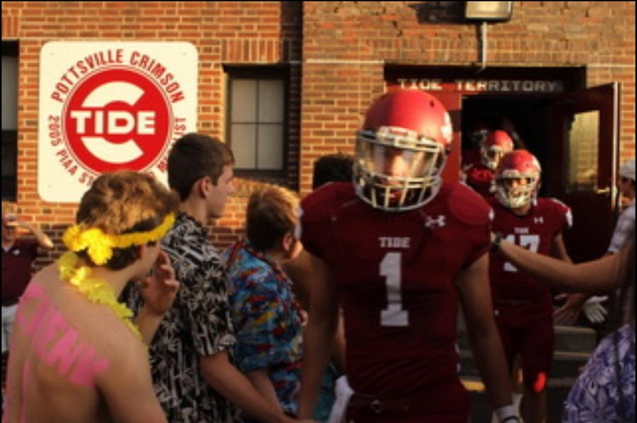 "Patrick Yoder high fives a student from PAHS while walking out of the locker room to enter the football field at Friday night's game. The Crimson Tide ended up winning against Blue Mountain 42-0. ""We are young to bring the energy we have had all year and double for games against Blue Mountain"" said Yoder."