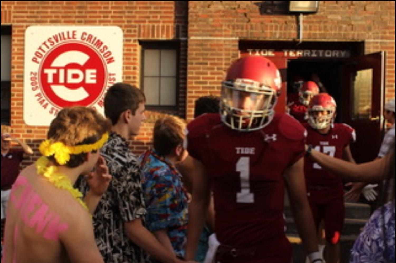 """Patrick Yoder high fives a student from PAHS while walking out of the locker room to enter the football field at Friday night's game. The Crimson Tide ended up winning against Blue Mountain 42-0. """"We are young to bring the energy we have had all year and double for games against Blue Mountain"""" said Yoder."""