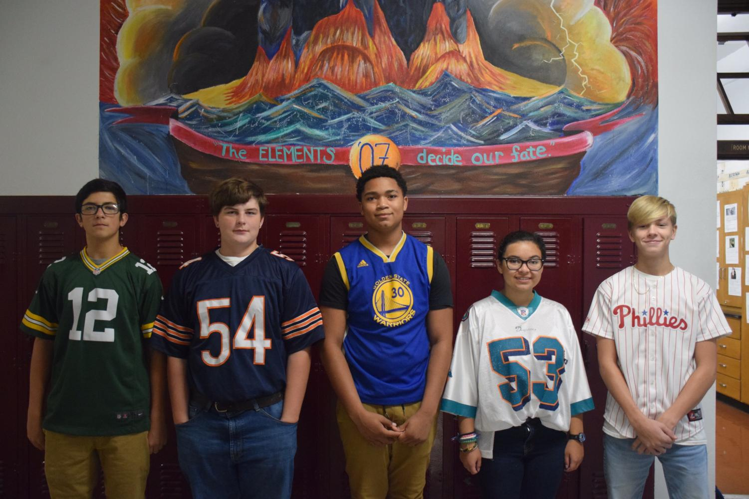 """Students participating in Red Ribbon week stand underneath the 2017 class mural. PAHS allowed students to wear their favorite team jersey or t-shirt on this day. Freshman Mason Major said, """"I grew up a Bears fan and the reason I wore that specific jersey is because I'm inspired by players on the Bears team."""""""