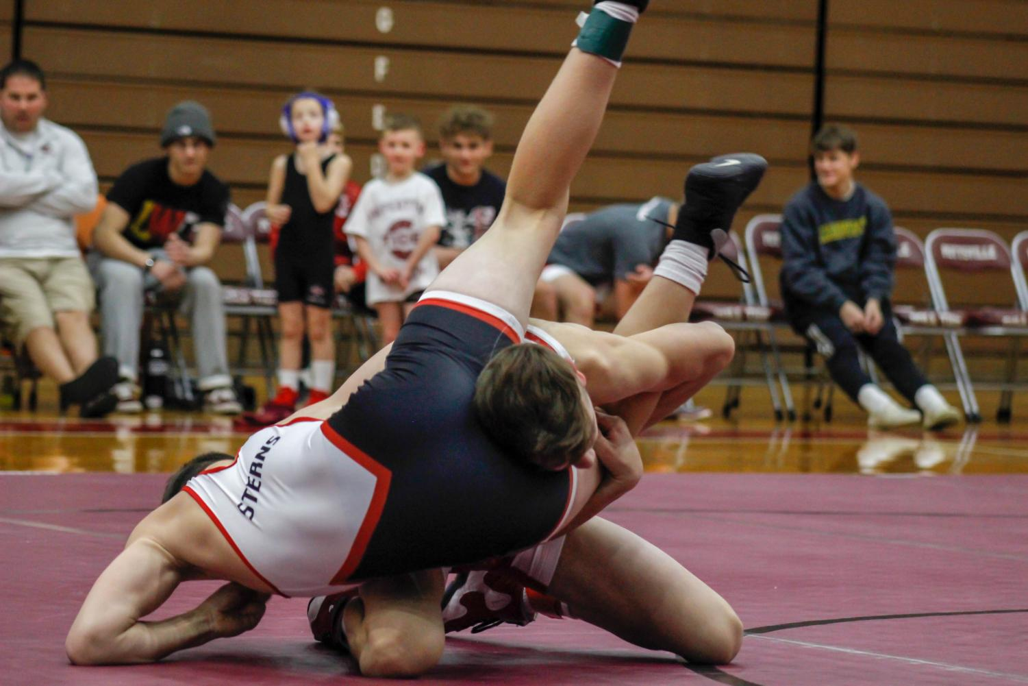 """On Sunday evening, freshman Dalton Monger attempts to pin teammate, junior Sammy Sterns. The proceeds from the event benefited the family of Jaden Leiby in paying for his medical bills. Teammate sophomore Bryce Shappell, who also wrestled that night, said, """"It felt good to wrestle for a great cause."""""""