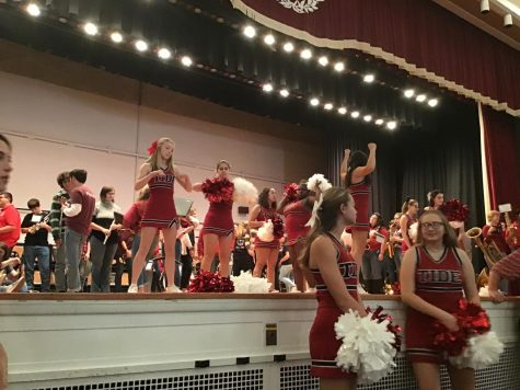 "Cheerleaders get ready to perform for the pep rally on stage in the auditorium. Tiana Green said, "" My favorite cheer we perform is of course everyone's favorite 'Give a Yell'. Everyone goes crazy and it's the best cheer around in my opinion""."