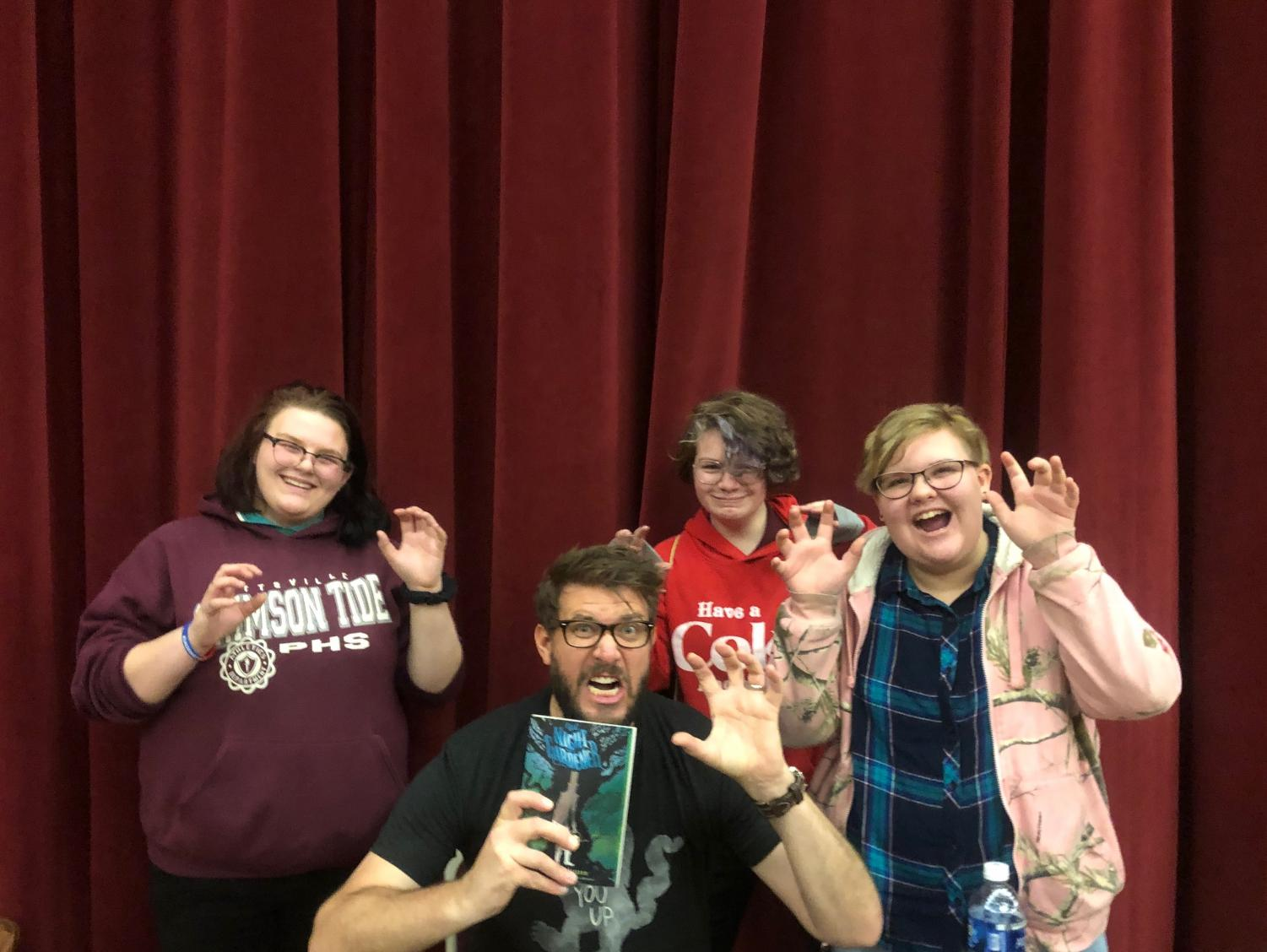 POSE - 8th graders Madison Auman, Jaden Ebert, and Catherine Lubinsky pose with author Jonathan Auxier at Teen Library Day at Kutztown University.
