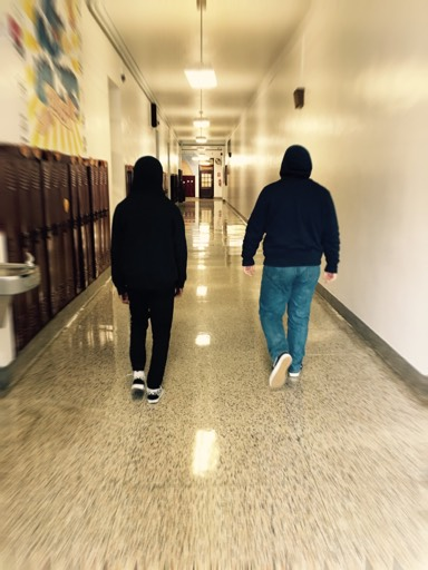 "Two students walk down the hallway at PAHS while wearing their hoodies with their hoods up. The Pottsville Area School District has had a strict 'no hoodie policy' since May 13 of 2009, and now has taken a next step to confiscate any hoodies worn during the school day. ""I'm not a big fan of the hoodie policy, but if a teacher would say to take it off, I do. But if it's very cold, I usually go through the day with the hoodie,"" sophomore Justice Lewis said."