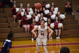 "Senior Matt Salata passes a ball to his teammate. The Crimson Tide lost this game with the final score of 70-49. Salata said, ""We're not the biggest team so we need to work on getting big and boxing out to limit offensive rebounds for the other team."""