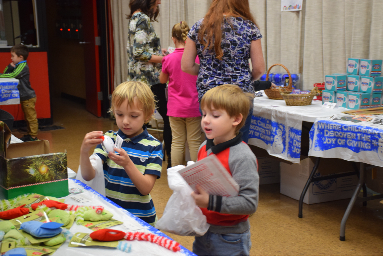 """Two kindergarten students from Mrs. Joyce's class browse for gifts for their friends and family. The Holiday Gift Shop began on December 4th and ended December 10th. Kindergarten student, Joseph Petrosky said, """"My favorite part of Christmas is Santa bringing him presents."""""""