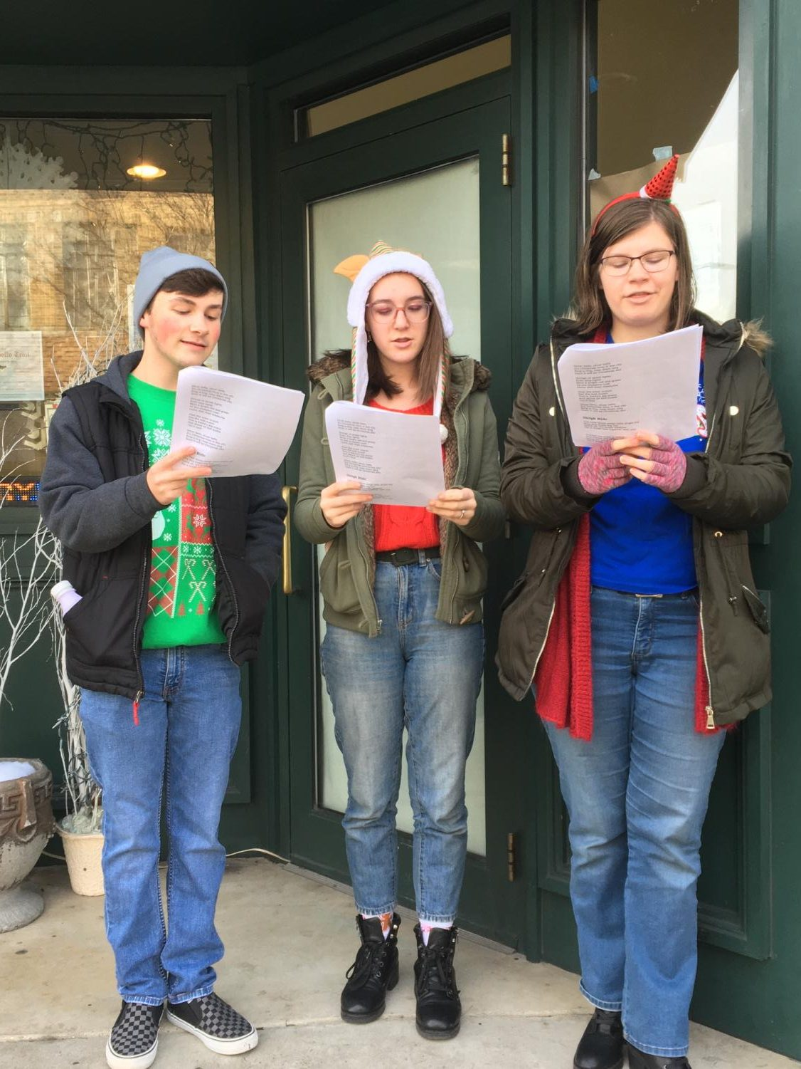 Junior Jake Montgomery, sophomore Alyssa Sheriff and Junior Julia Malek sing Christmas carols in front of the Majestic Theatre in downtown Pottsville. The PAHS Crimson Players spent time singing for