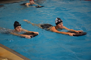 "Sophomore Jadyn Wagner, left, and junior Lizzie Donovan, right, both hold a kickboard  during practice. Wagner just began swimming. ""Jadyn has improved greatly with her swimming abilities since she just joined the team,"" coach Mr. Greg Schuettler said."