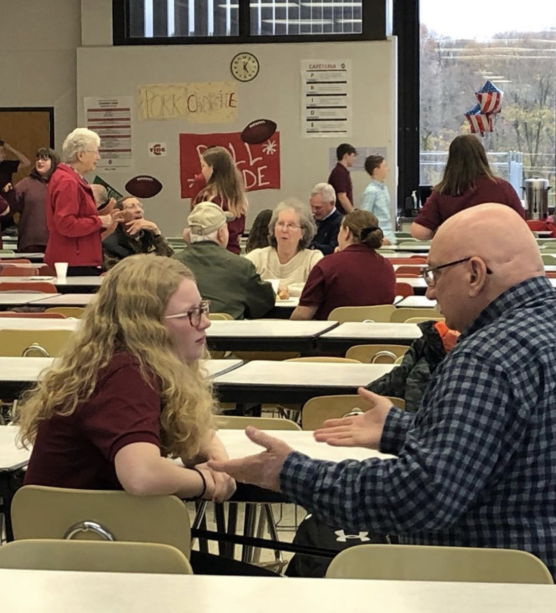 DISCUSS - 8th grader Chase Teresavage talks with her grandfather at the DHHL Veterans' Day breakfast event.