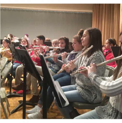In a photo from before the pandemic, flute players read music and pay attention to the directors during a symphonic band rehearsal.