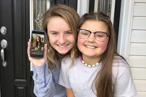 "(From left to right Allie Miske, Greta Snukis, Ava Stankavage) Allie, Greta, and Ava pose in front of the festive fall door. If a person couldn't see their family members in person, they had the option of FaceTiming them or talking to them in during a zoom call. Senior Greta Snukis said,""Every year at almost every holiday, my cousins and I get a photo in front of my aunt's door. My cousin, Allie, was unable to attend our celebration because of her being in a different state. So we put her on FaceTime and found a way to still get the photo."""
