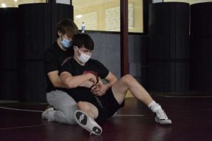 "Nativity Senior, Matt Ross is in action at wrestling practice getting ready for the season. The wrestlers had to adapt to wearing masks during practice. Ross said, ""Most of us have things we can do to stay ready for the season at our houses so it won't affect us too much."""