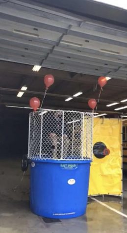 "Make r. Maley sits nervously on top of a dunk tank platform and waits to be dunk= ed into the cold water. This was a challenge done by the reading department at the elementary to see how many books students could read. Maley said, ""I was told that they have a decent turn-out, but we really wanted to get more kids reading.   We are also trying to keep the virtual students engaged."""