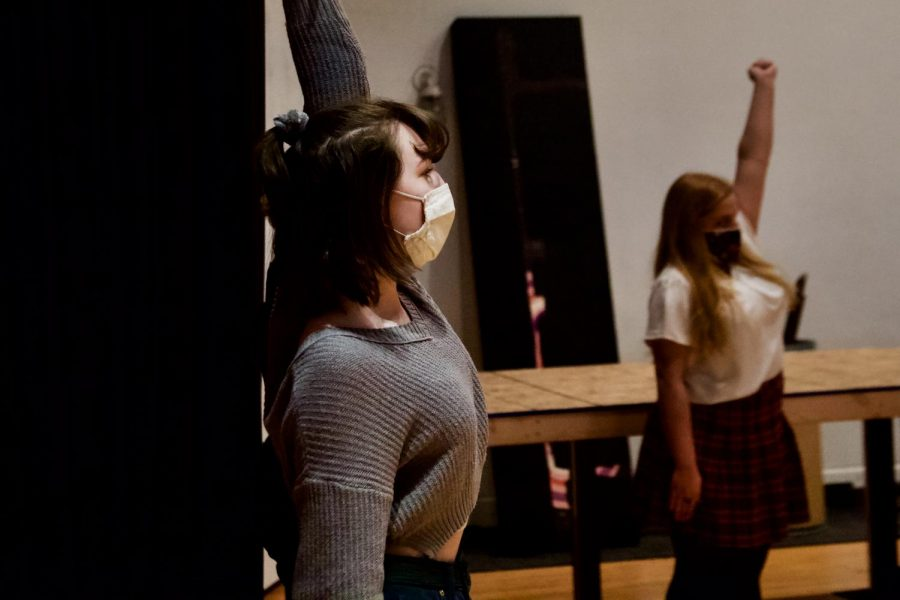 """The drama club is warming up with physical and vocal workouts before rehearsals. Alyssa Sherrif and Annabelle Chaklos stretch before rehearsal on Monday, March 22. Alyssa says, """"I am very happy to participate in this musical. Drama club has always been something that I look forward to on a daily basis!"""""""