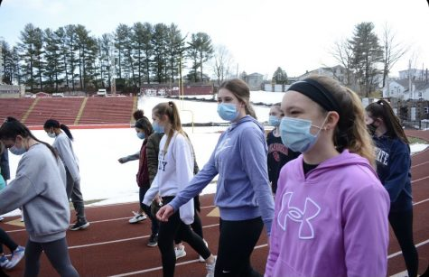 "Junior Kaylee Becker and Emilee Rose are seen warming up their ankles at track practice.  Due to COVID there are restrictions at practice to wear a mask and social distance as much as possible. Junior Emilee Rose said, "" The first practice was definitely different from previous years, but I'm thrilled to be back to practice."""