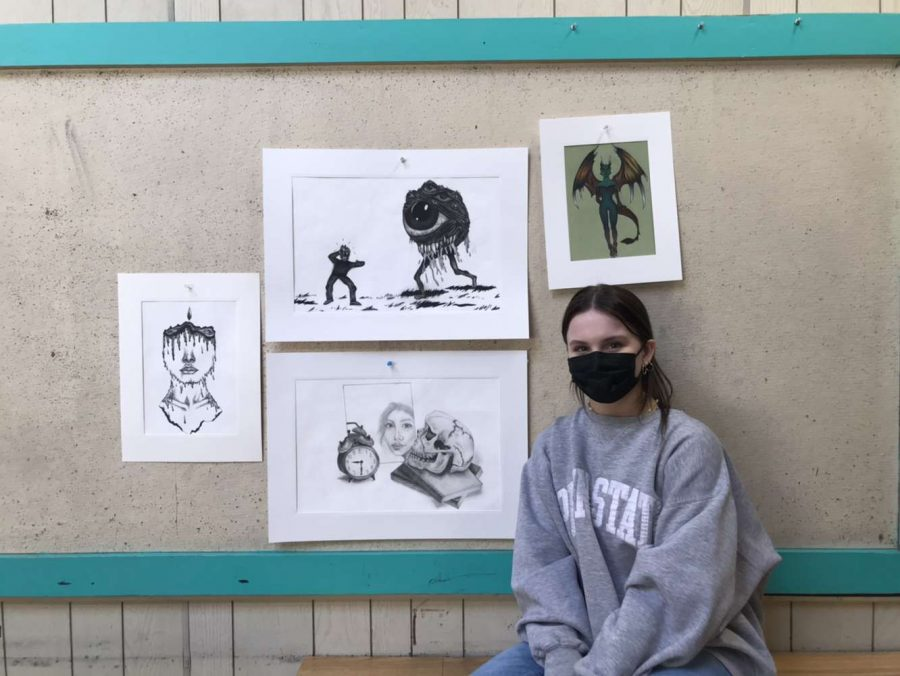 Artist Grace sits in front of her work. Her favorite piece is to the far left!