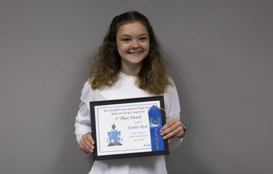 """Junior Emilee Rose stands proud while holding her new award from the media and design logo competition. Emilee won the regional competition this year and now advances to states. She said, """"I found an interest in doing the competition because my brother Parker also did it."""""""