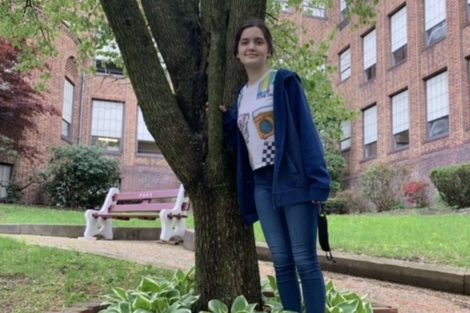 """Sophomore Rene Keiter stands near a tree to celebrate Earth Day. Many students at PAHS honor the earth by not littering and making small changes to help the environment. Rene said """" I think the significance of Earth Day is a day to recognize the importance of the planet."""""""