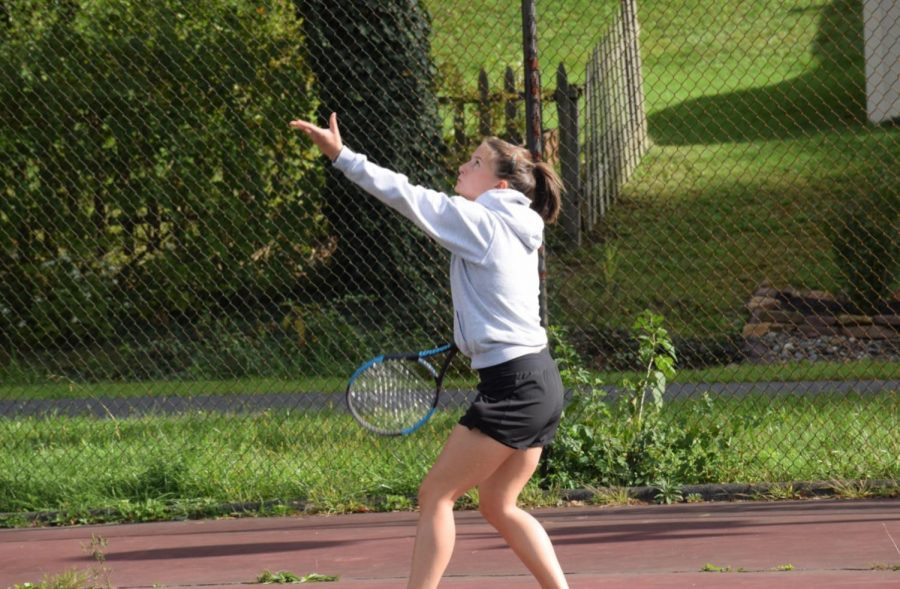 """Elise Gilot throws the ball up to serve at practice. On September 31 after school Elise Gilot was at practice. Gilot said, """"I really like tennis, it's one of my favorite sports. It is a very difficult sport both physically with the movements and especially the leg placements and mentally because it is an individual sport which means that if you miss something or do something wrong, it is very frustrating."""""""